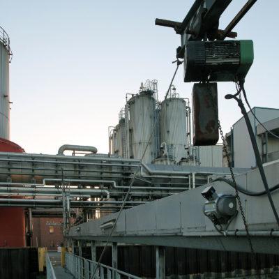Ein Kran am Schiffsanleger hilft die Schläuche zum Entsorgungsfahrzeug zu heben.