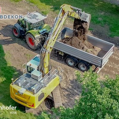 Autonomer Bagger belädt nach selbstständig durchgeführtem Aushubvorgang ein autonom herbeigefahrenes Transportfahrzeug (Traktor mit Anhänger) mit Erdaushub. (Autonome Systeme des Fraunhofer IOSB) (Foto: ROBDEKON / Fraunhofer-Institut für Optronik, Systemtechnik und Bildauswertung IOSB)