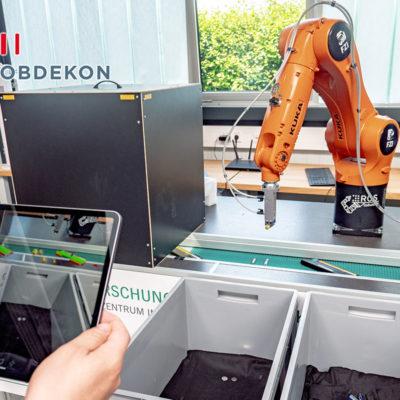 Förderband des FZI Karlsruhe mit Scaneinheit zur 3D-Erfassung und Klassifikation der verschiedenen Batterietypen auf dem Band. Der Roboterarm mit Greifer sortiert die Batterien anschließend in unterschiedliche Behälter. (ROBDEKON / Fraunhofer-Institut für Optronik, Systemtechnik und Bildauswertung IOSB)